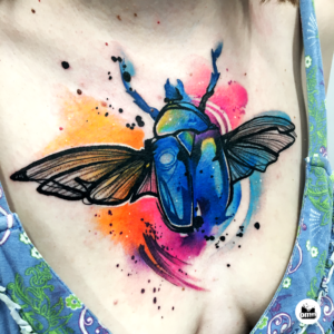Niebieski tatuaż akwarelowy żuka na dekolcie