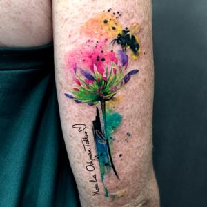 Piegi na tatuażu akwarelowym kolorowym kwiatka z pszczołą